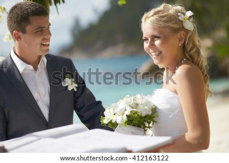 Beautiful, gorgeous wedding couple during ceremony on the beach. Smiling and playing with each other, posing and shining with happiness, holding bridal bouquet.  - stock photo
