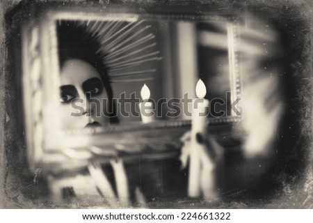 Beautiful goth girl holding candle in hand and looking into the mirror. Grunge texture effect - stock photo