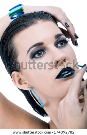 Beautiful graceful naked woman in black Gothic makeup with black nail lacquer and lipstick and heavy eyeliner wearing stylish earrings and bracelet posing looking at the camera, isolated on white