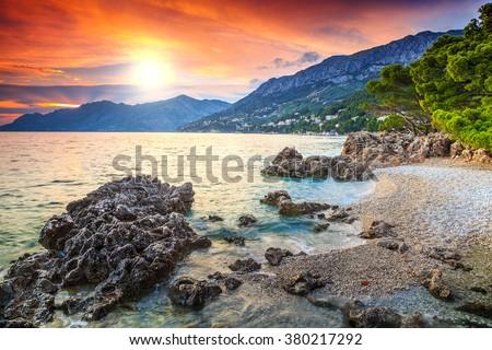 Beautiful gravel beach with Biokovo mountains on background and stunning colorful sunset,Brela,Makarska riviera,Dalmatia,Croatia,Europe - stock photo