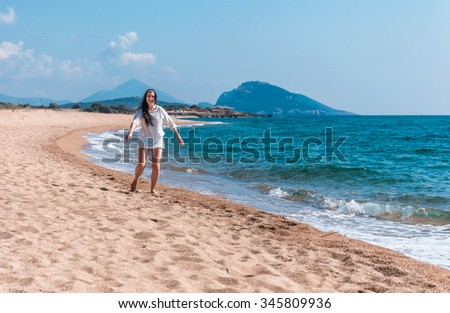 beautiful greek young brunet woman  walking on a beach in white dress