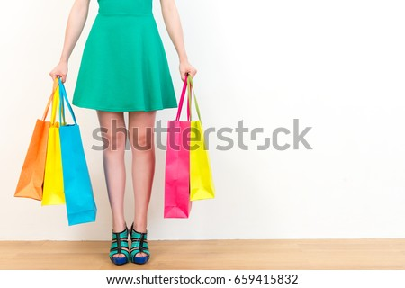 beautiful green dress woman showing lot of shopping bags standing on wooden floor with white wall background empty area.