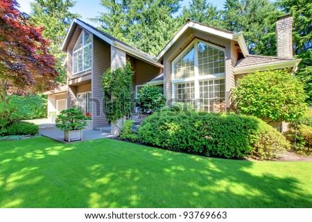 Beautiful green front garden with brown house and shrubs. - stock photo