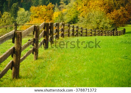 Beautiful green grass meadow with wooden fence in the Alps. Colorful scenic background. - stock photo