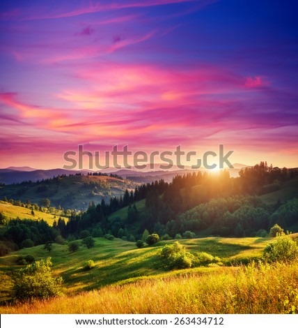 Beautiful green hills glowing by warm sunlight at twilight. Dramatic scene. Colorful sky, red clouds. Carpathian, Ukraine, Europe. Beauty world. - stock photo