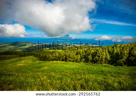 Beautiful green landscapes with wind power generators along the ocean in Faial island, Azores, Portugal - stock photo