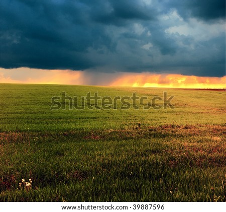 Beautiful green meadow with storm clouds and thunderstorm - stock photo