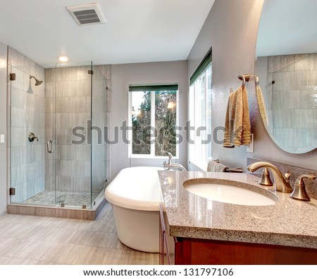 Beautiful grey new modern bathroom interior with glass shower and tub. - stock photo