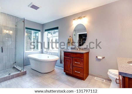 Beautiful grey new modern bathroom interior with two separate sinks, tub and glass shower. - stock photo