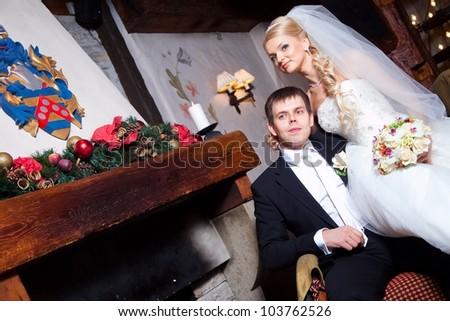 beautiful groom and bride  sitting near fireplace on wedding day - stock photo