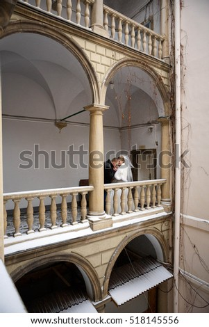 Beautiful groom and bride standing on balcony together
