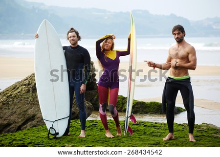 Beautiful group of surfers preparing for surf session and having fun, surfers standing on the beach with ocean waves on background - stock photo
