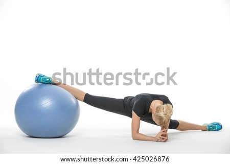 Beautiful gymnast girl in the sportswear with a blue fitball on the white background in the studio. She wears cyan-yellow sneakers, black pants and black t-shirt. She makes the splits: she leans on