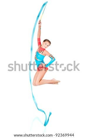 Beautiful gymnast jumping with ribbon - stock photo
