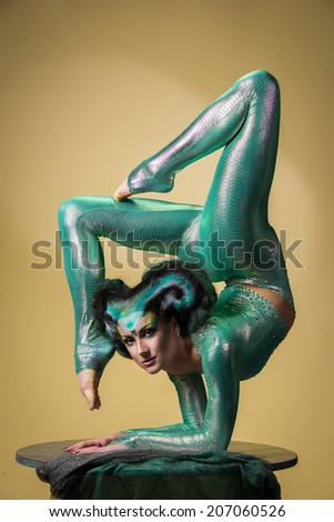 Beautiful gymnast performs an acrobatic trick on a stand as a snake - stock photo