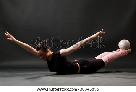 beautiful gymnast with ball against dark background - stock photo