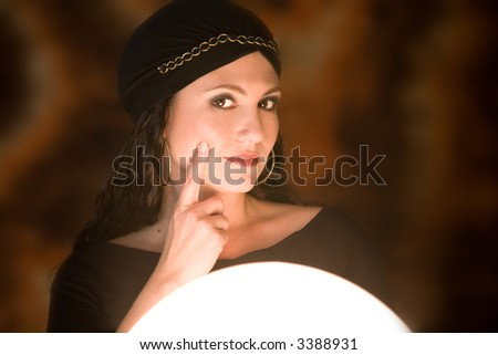 Beautiful gypsy girl with her crystal ball looking dubious - stock photo