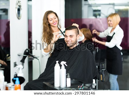 Beautiful hairdresser making a stylish haircut with sharp scissors for a man in a hair studio - stock photo