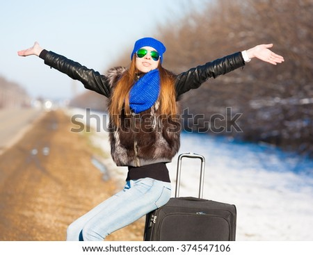 Beautiful haired sexy woman, dressed blue jeans, hat and scarf, fur jacket, sunglasses. Has long hair and elegant slim body, walking to road and holding suitcase. Portrait urban city. Real lady. - stock photo