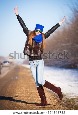 Beautiful haired sexy woman, dressed blue jeans, leather boots, fur jacket, sunglasses. Has long hair, legs and elegant slim body, walking to road, go in hitch-hiking. Portrait urban city. Real lady. - stock photo