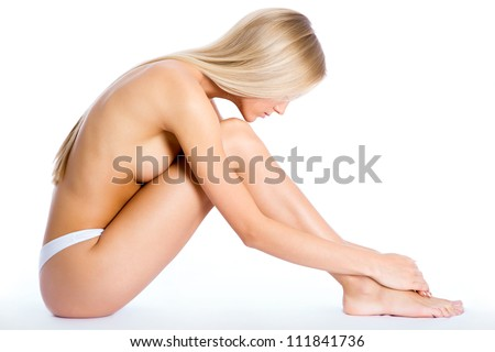 Beautiful half-dressed woman sitting on a white background - stock photo