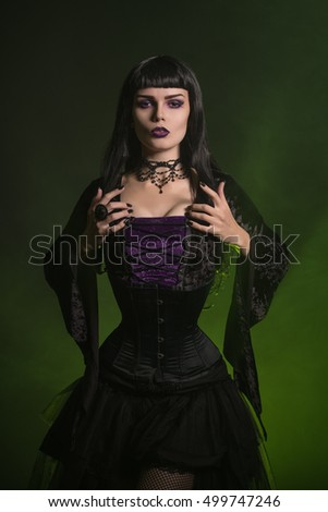 Beautiful Halloween witch dressed in a corset and velvet blouse, studio shot