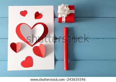 Beautiful hand made post card and pen on color wooden background - stock photo