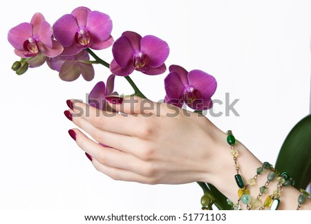 Beautiful hand with pink manicure, green beads touching orchid - stock photo