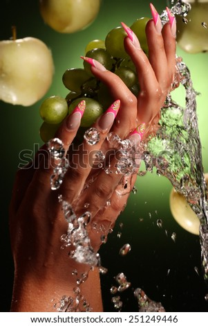 beautiful hands and nails on green background . Beautiful Female Hands.Manicure concept