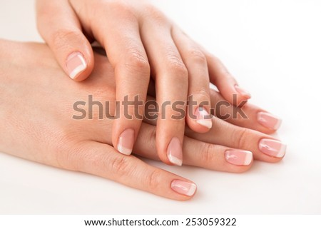 Beautiful hands with french manicure on white background