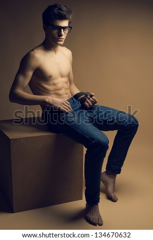 Beautiful (handsome) muscular male model with nice abs in jeans posing in trendy glasses and getting undressed. Boy sitting on a wooden cube. Vogue style. Fashion studio portrait.