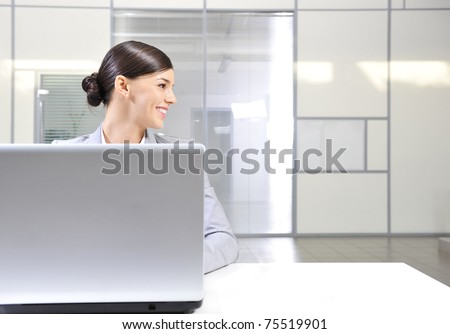 Beautiful happy and smiling business woman working on computer at her office and looking right from the camera - stock photo