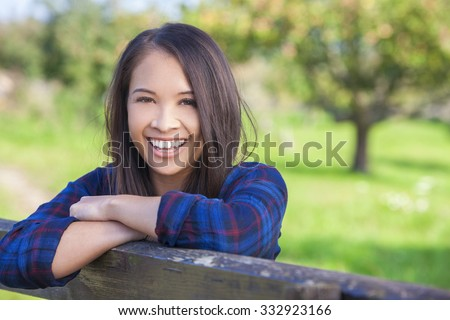Beautiful happy Asian Eurasian young woman or girl wearing denim shirt, smiling and leaning on fence in sunshine - stock photo