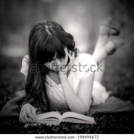 Beautiful happy Asian girl lies on meadow and reads the book , Happy smiling beautiful young university student studying lying down in grass. black and white portrait - stock photo