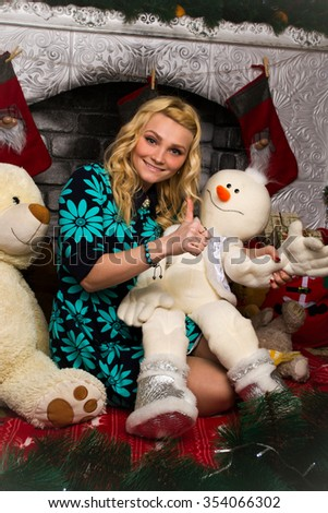 Beautiful,happy,blonde,attractive,impressive,charming,pleasant-looking girl has a finger up with a snowman in the winter studio with fireplace,socks,fir-trees,says,everything is ok,show,adult,smile - stock photo