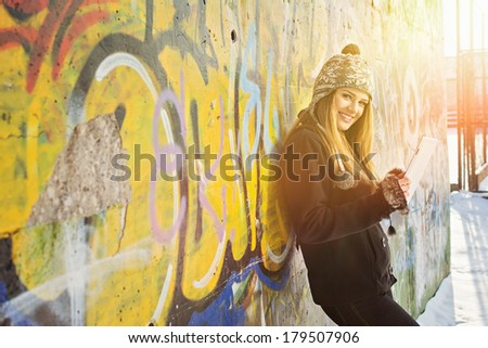 Beautiful happy blonde Caucasian teenage girl using tablet computer. Cute teenager with tablet pc against graffiti wall outdoors in winter. Technology and modern lifestyle. - stock photo