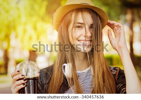 Beautiful happy blonde teenage girl holding cup of takeaway coffee. Young woman with hat and headphones smiling enjoying autumn. Medium retouch, vibrant colors, horizontal. - stock photo