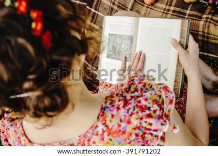 beautiful happy bride and stylish retro groom, reading books and relaxing, eating fruits,  picnic in sunny meadow - stock photo