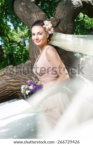 beautiful happy bride in beige dress smiling standing among green trees - stock photo