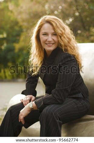 beautiful happy business woman resting after successful transaction in the park - stock photo
