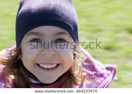 Beautiful happy child on a background of green grass close-up