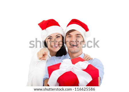 beautiful happy christmas holiday couple love smiling embracing in red new year hat cap, man and woman hold gift box present smile point finger at you looking at camera, isolated over white background - stock photo