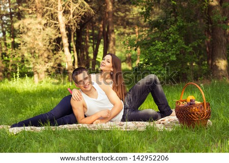 beautiful happy couple at picnic. outdoors portrait in forest park - stock photo