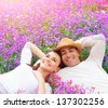 Beautiful happy couple lying down on purple lavender field, having fun on floral glade, summer nature, love concept - stock photo