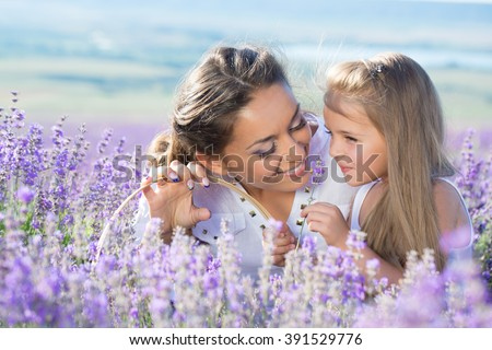 Beautiful happy couple mother and her  cute daughter  in lavender field - stock photo