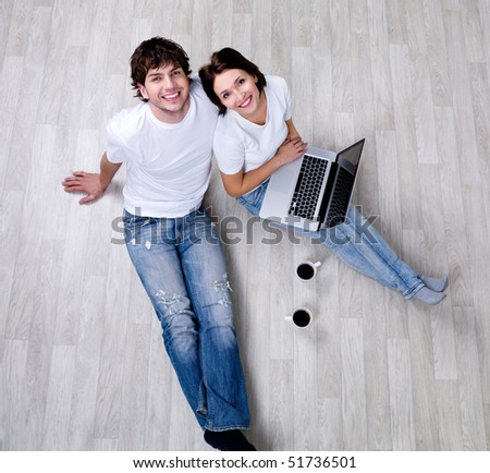 Beautiful happy couple sitting on the floor in new home with laptop - high angle view