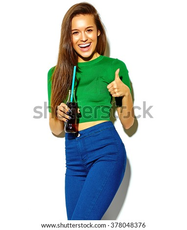 beautiful happy cute brunette woman girl in casual green hipster summer clothes with no makeup isolated on white drinking cola from bottle with straw showing thumbs up sign - stock photo