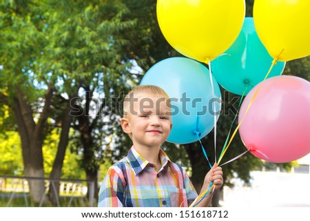 Beautiful happy cute joyful smiling blond child (little boy) with bunch of balloons in hands, close up outdoor portrait, birtday, fun and summer holiday.