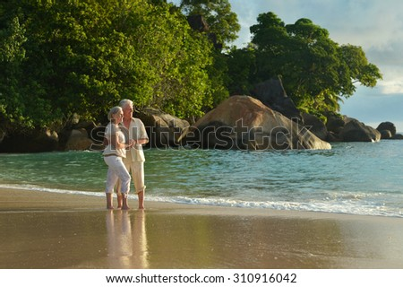 Beautiful happy elderly couple rest at tropical resort - stock photo