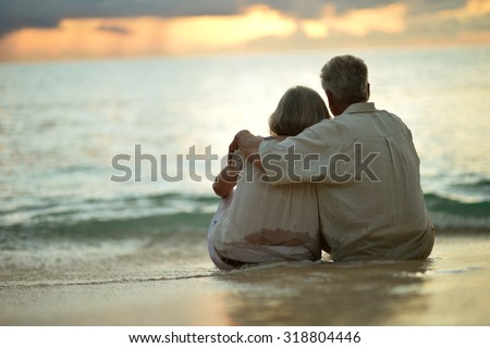 Beautiful happy elderly couple rest at tropical resort,back view - stock photo